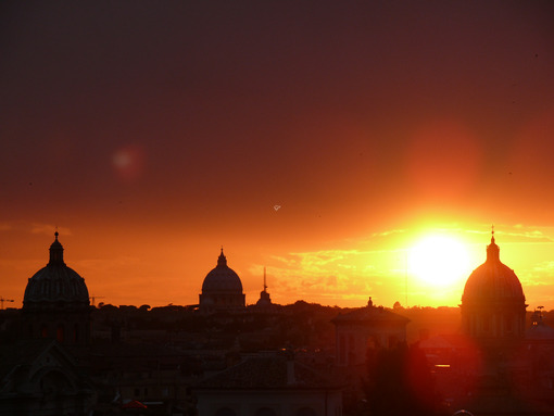 Skyline with the setting sun over Rome's rooftops seen from the Caffarelli terrace. Church domes and city profile. - MyVideoimage.com