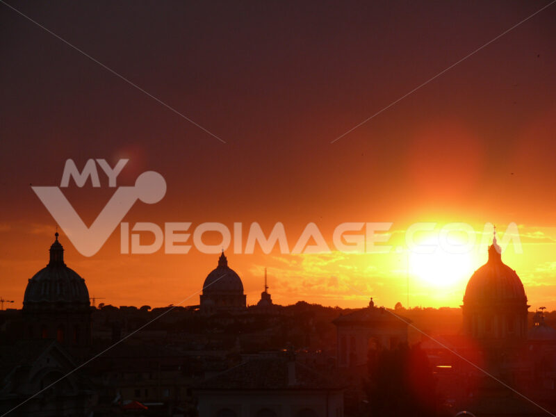 Skyline with the setting sun over Rome's rooftops seen from the Caffarelli terrace. Church domes and city profile. Città italiane. Italian cities.