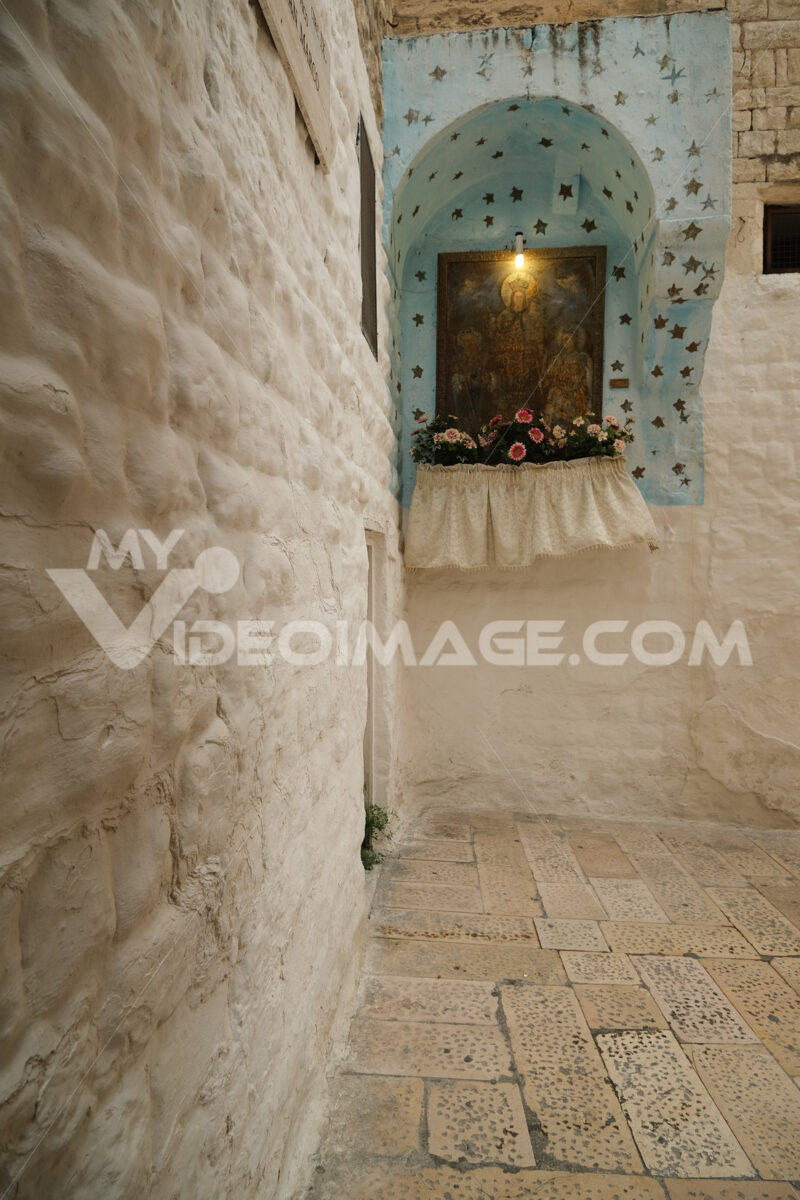 Small altar with flowers and painting with Madonna in an alleyway in Bari. The wind blows and moves a cloth. - MyVideoimage.com