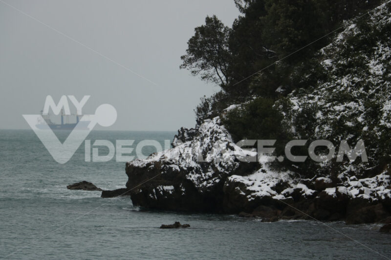 Snow fell on the rocky coast of Liguria near the Cinque Terre. In the background a cargo ship in the middle of the sea. - LEphotoart.com