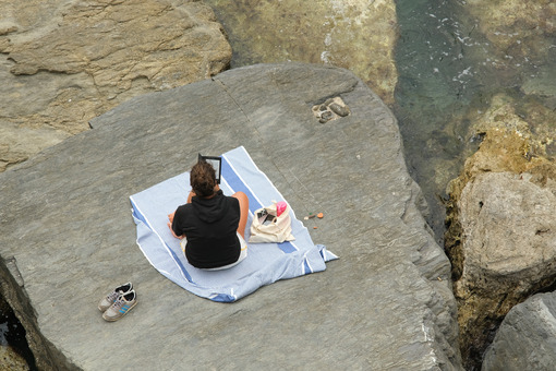 Social distancing. Young woman at the sea on the cliff. - MyVideimage.com