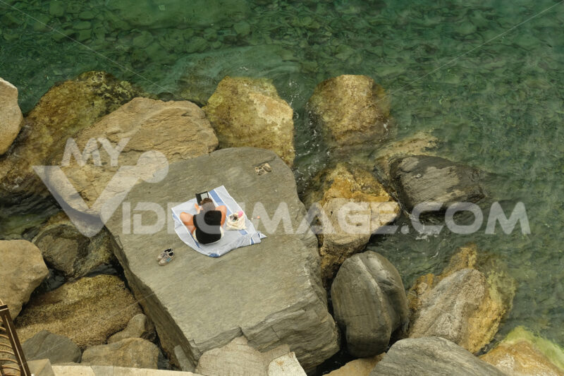 Social distancing. Young woman at the sea on the cliff. - LEphotoart.com