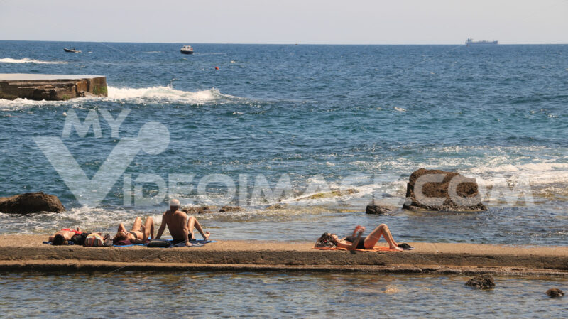 Some people sunbathe out on the pier in the sea of Livorno. Pano - MyVideoimage.com