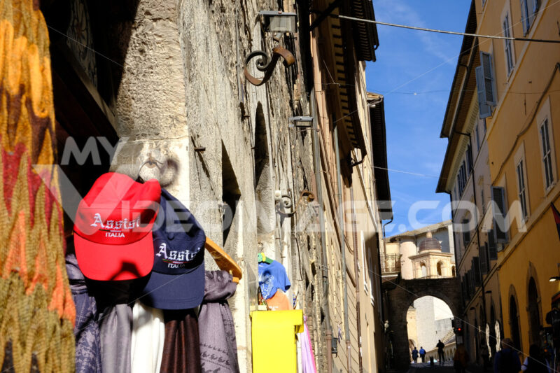 Souvenir shop with hats hanging on the door in the ancient city of Assisi. - MyVideoimage.com