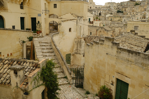 Stairway in a street of the ancient city of Matera. Beige stone paving and houses in tuff blocks. - MyVideoimage.com