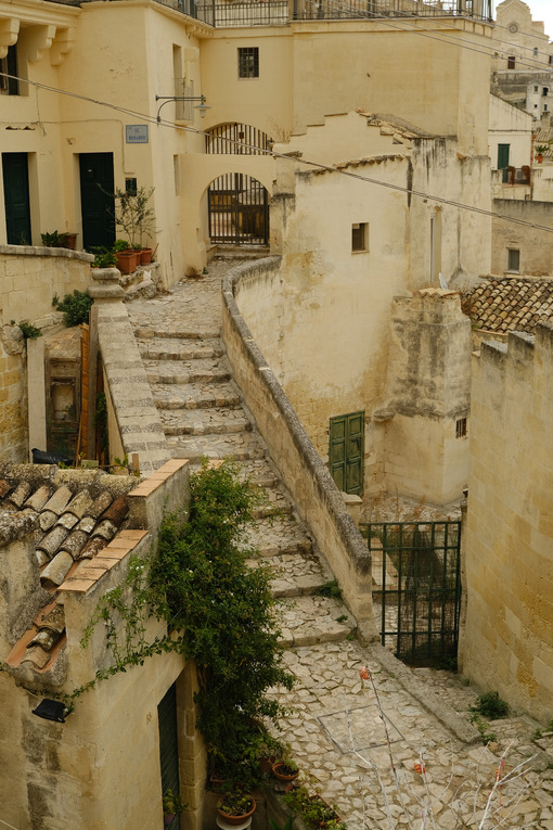Stairway in a street of the ancient city of Matera. Beige stone paving and houses in tuff blocks. - MyVideoimage.com | Foto stock & Video footage