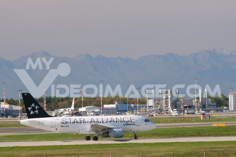 Star Alliance Lufthansa Airbus A319-100 on the Malpensa airport runway. In the background the mountains of the Alps. - MyVideoimage.com