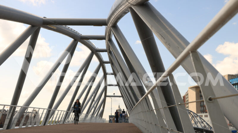 Steel pedestrian bridge over a canal in Amsterdam. A tourist boa - MyVideoimage.com