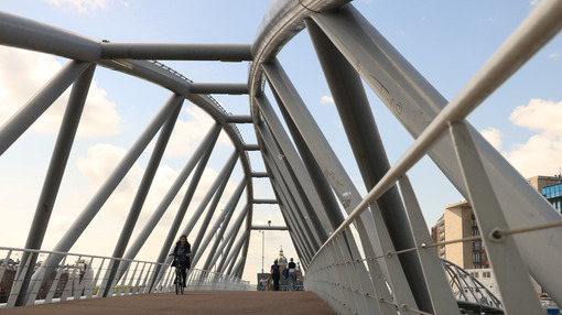 Steel pedestrian bridge over a canal in Amsterdam. A tourist boa - MyVideoimage.com