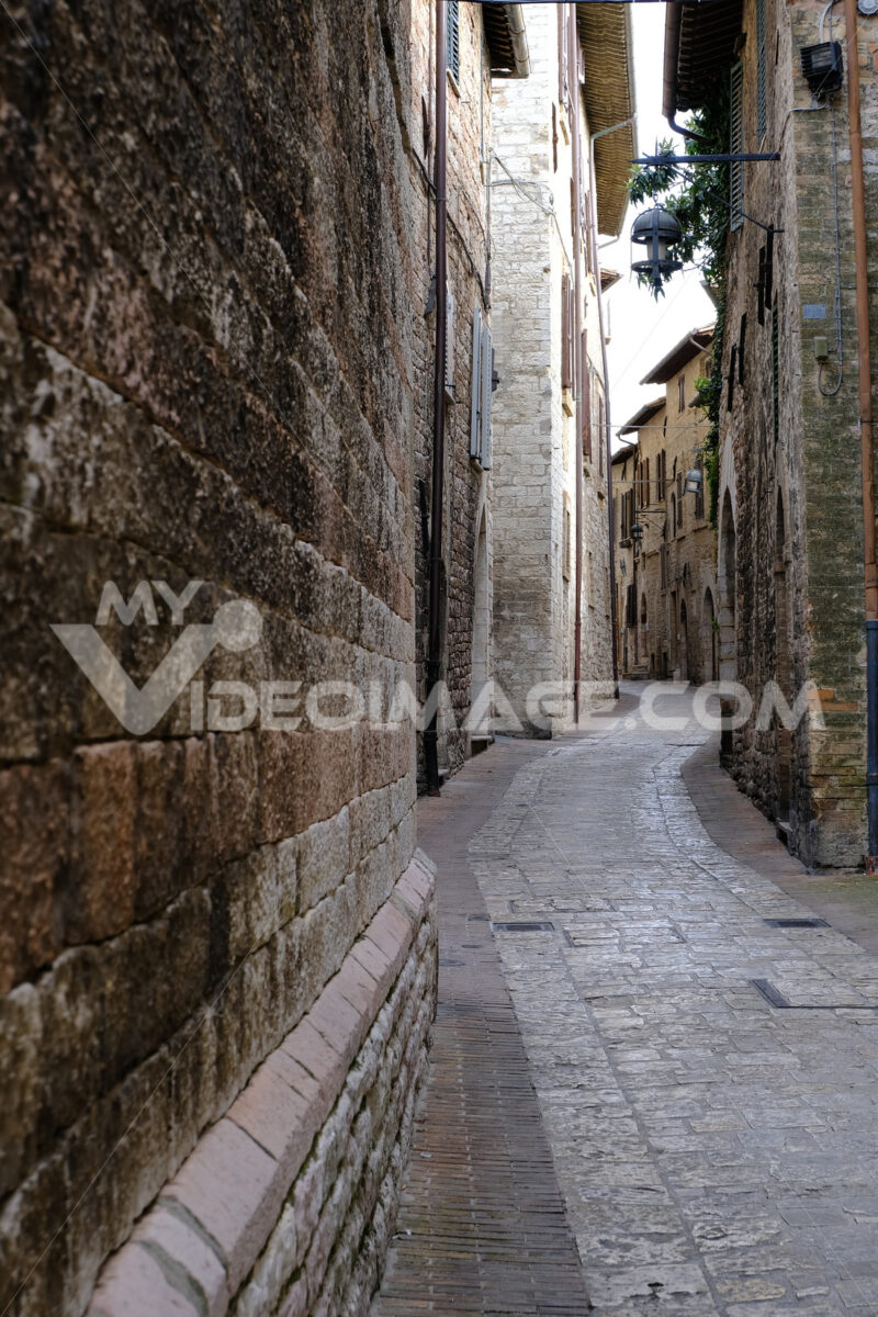 Strada deserta ad Assisi. Alley of the city of Assisi with stone facades of historic houses. Narrow alleys of the city with the walls of the stone houses. Deserted road. - MyVideoimage.com | Foto stock & Video footage