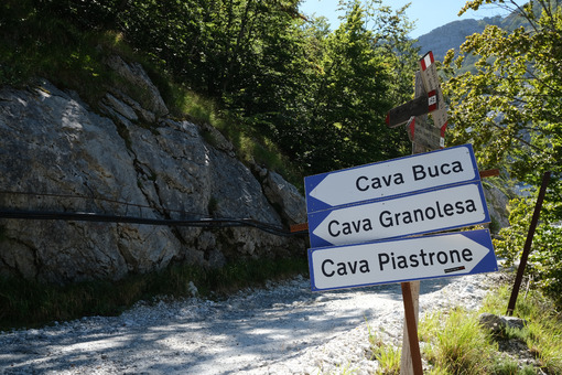 Strada sterrata bianca. Dirt road carved into the rock and trail signs in the Apuan Alps. - MyVideoimage.com | Foto stock & Video footage