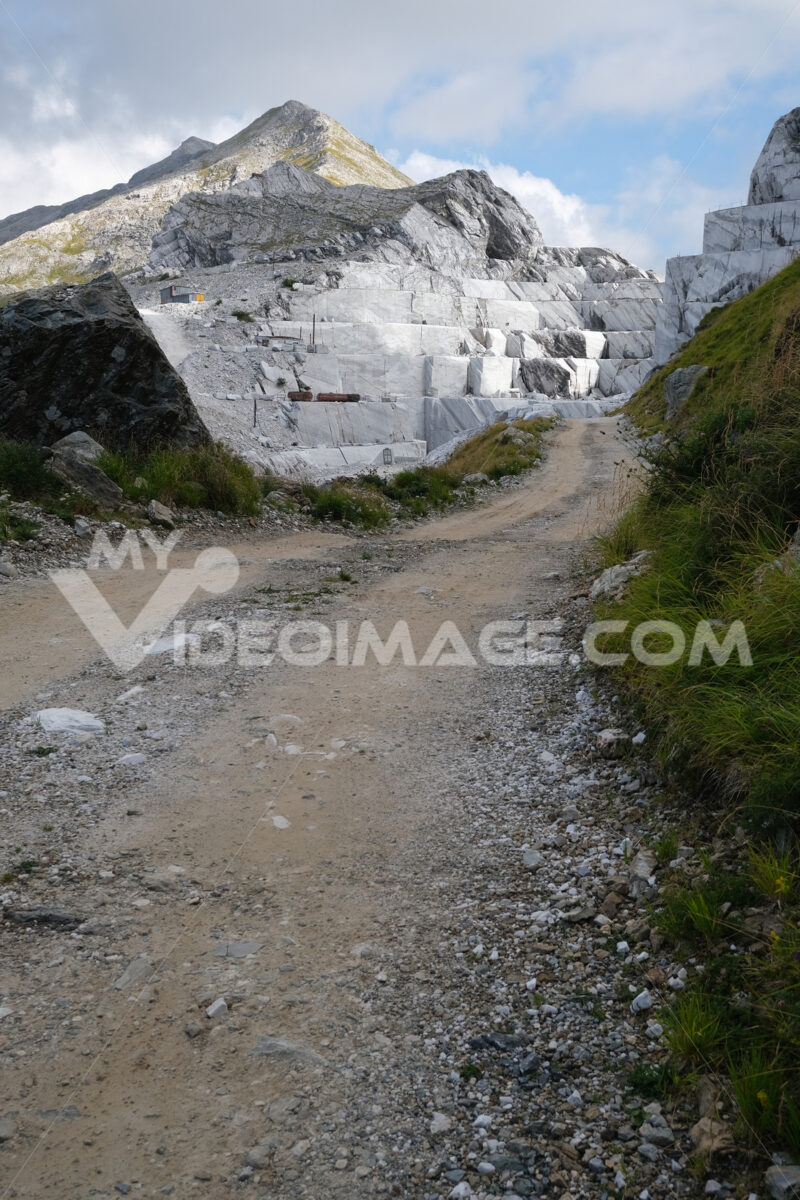 Strada sterrata sulle Alpi Apuane. White road leads to a marble quarry on the Apuan Alps in Tuscany.  Foto stock royalty free. - MyVideoimage.com | Foto stock & Video footage
