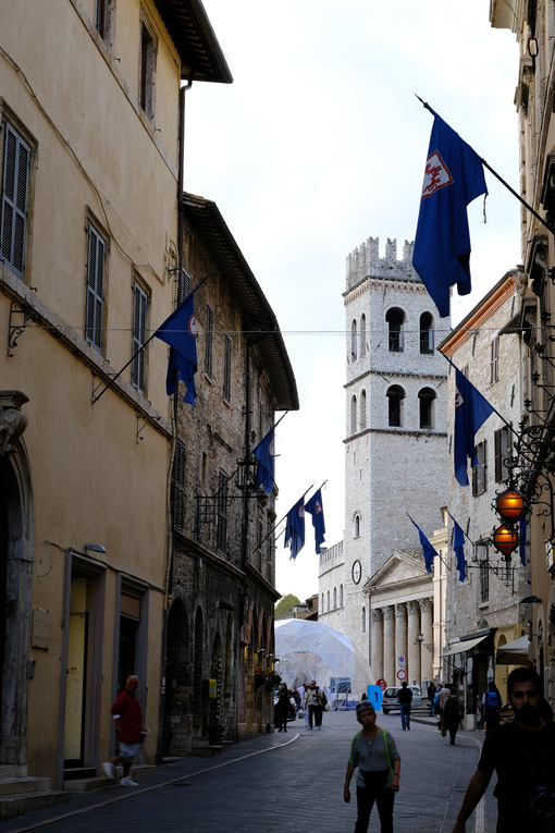 Street in the city of Assisi with the background of the civic tower and the temple of Minerva. Flags and people in the foreground. - MyVideoimage.com