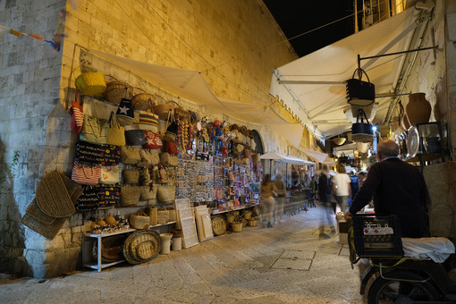 Street in the historic center of Bari with market for tourists. Bags and souvenirs in an alley with night lights. - MyVideoimage.com | Foto stock & Video footage