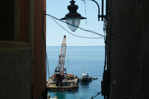 Street lamp and barge with crane for dredging the seabed at the port of Riomaggiore, Cinque Terre, royalty free - MyVideoimage.com | Foto stock & Video footage