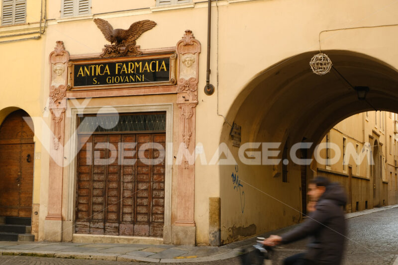 Street with arch and pharmacy shop with ancient sign with eagle. - MyVideoimage.com