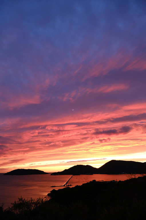 Sun setting over the sea with red and blue clouds. Gulf of La Spezia, Mediterranean Sea in Liguria. - MyVideoimage.com