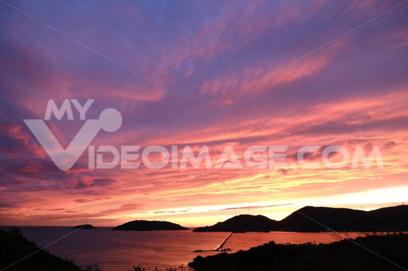 Sun setting over the sea with red and blue clouds. Gulf of La Spezia, Mediterranean Sea in Liguria. - MyVideoimage.com