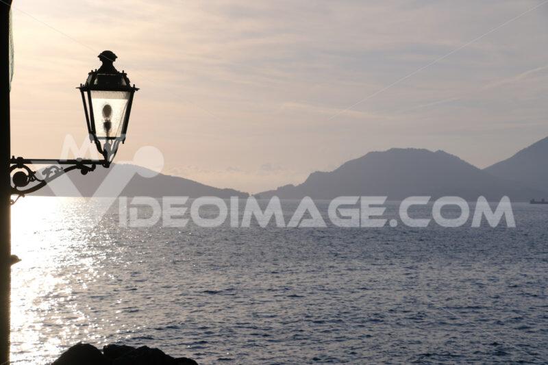 Sunset light on the sea of the Gulf of La Spezia. Street lamp in the marine village of Tellaro, near the Cinque Terre. - MyVideoimage.com