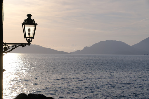 Sunset light on the sea of the Gulf of La Spezia. Street lamp in the marine village of Tellaro, near the Cinque Terre. - MyVideoimage.com