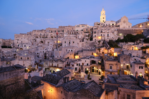 Sunset lights in the city of Matera. Bell tower, church and typical houses called Sassi. - MyVideoimage.com