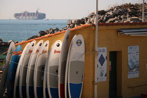Surfboards placed on the shore and a container ship in the background. - MyVideoimage.com