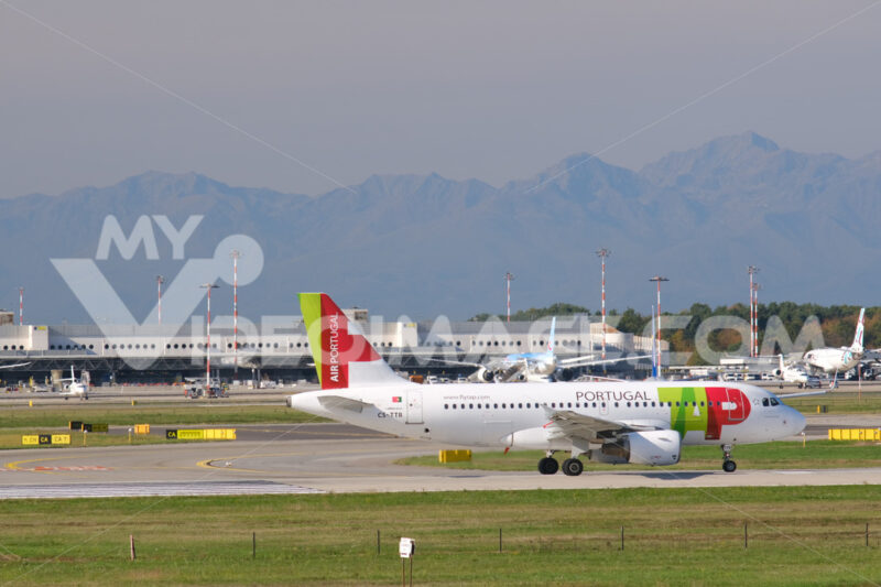 TAP Portugal Airbus A319-112  airplane on the Malpensa airport runway. In the background the buildings of Terminal 1 and parked airplanes. - MyVideoimage.com