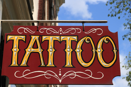 Tattoo shop sign. Red panel with blue sky. - MyVideoimage.com
