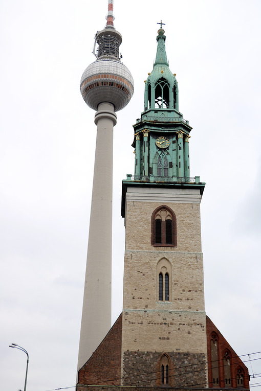 The Alexanderplatz TV tower next to the bell tower of a historic - MyVideoimage.com