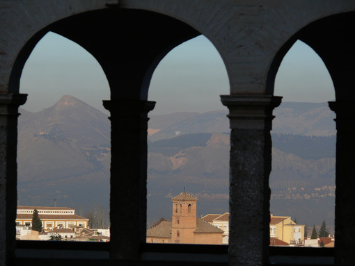 The city of Granada framed by the arches of a portico. Granada foto. Granada photo