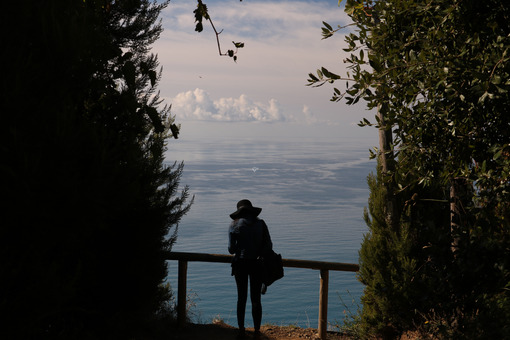 Tourist admires the marine landscape of the Cinque Terre in Liguria. - LEphotoart.com