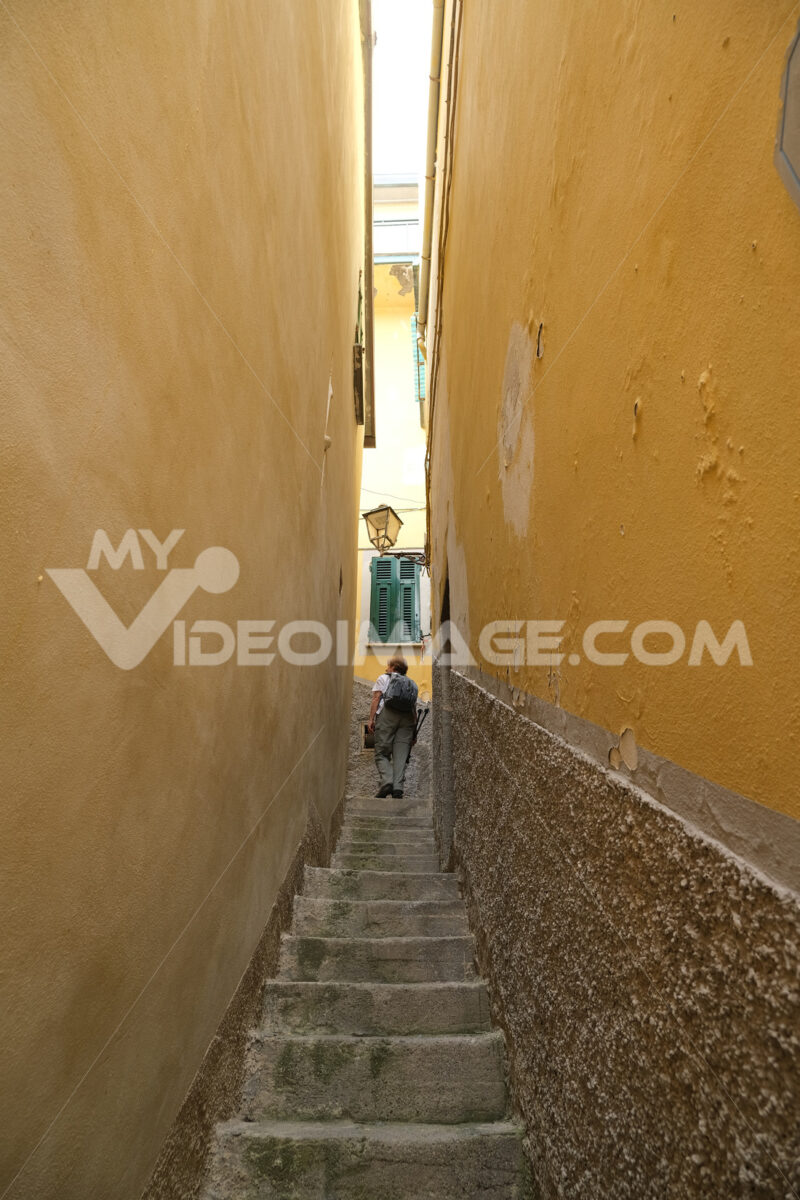 Tourist climbs a steep staircase in a narrow alley in the center of the village. - LEphotoart.com
