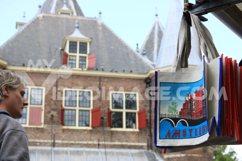 Tourist market in the city center. Bags for sale hanging from the stall. - MyVideoimage.com