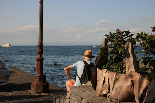 Tourist with hat, sitting watching the blue sea. - MyVideoimage.com