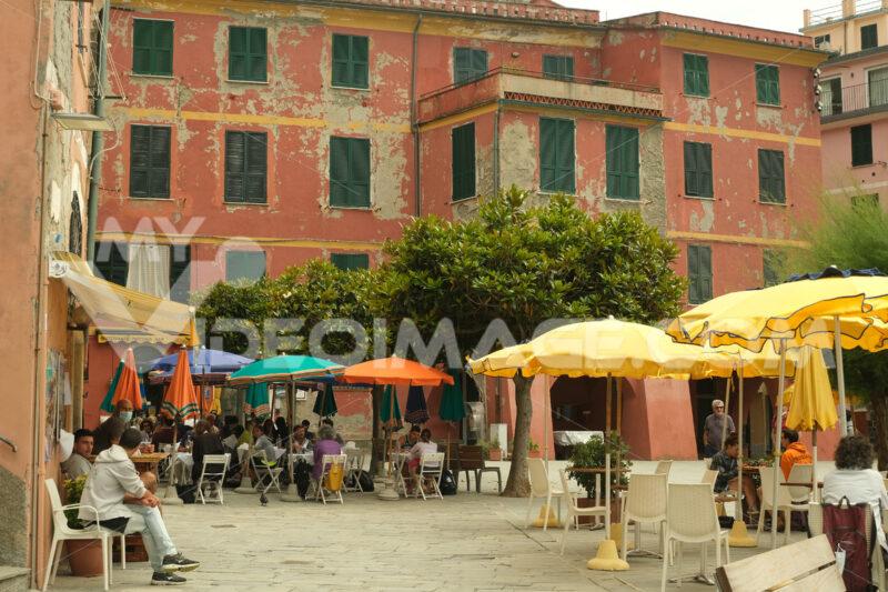 Tourists sitting at restaurant tables in the town square. Coronavirus Covid-19 pandemic period. Città italiane. Italian cities.