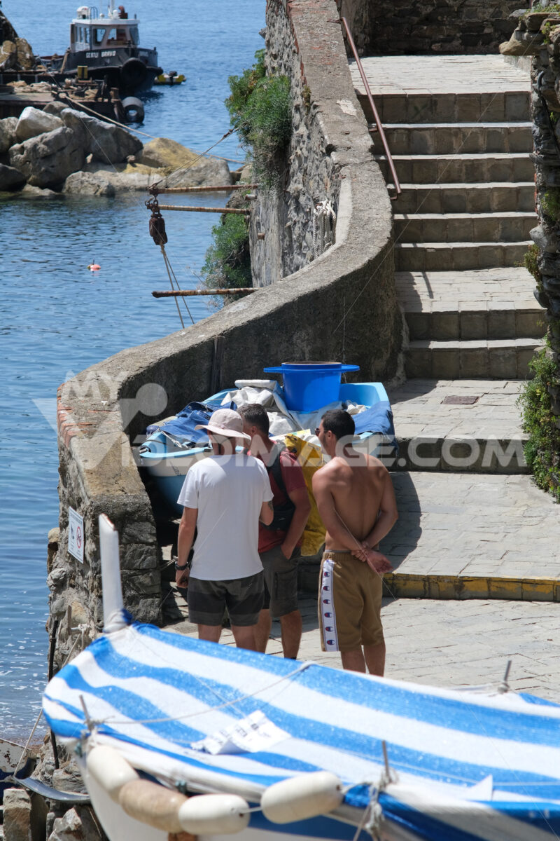 Tourists with rucksacks stopped for a stop in front of the sea in the town square. In the background the path with stairs. - MyVideimage.com