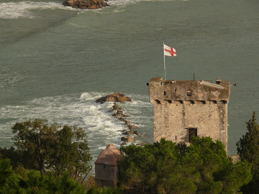 Tower of the castle of San Terenzo in Lerici with the flag of Genoa in the wind. In the background the sea. Foto mare. - LEphotoart.com