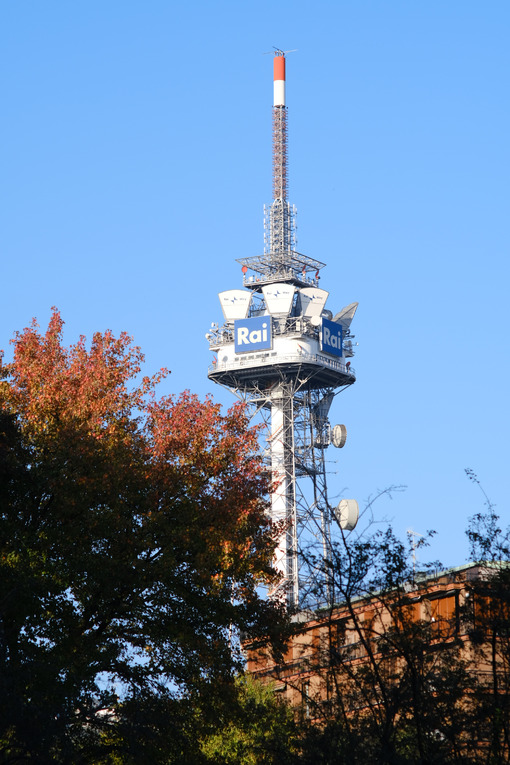 Tower with antennas and TV radio repeaters of the RAI of Milan. In the foreground trees with falling leaves. Società. - LEphotoart.com