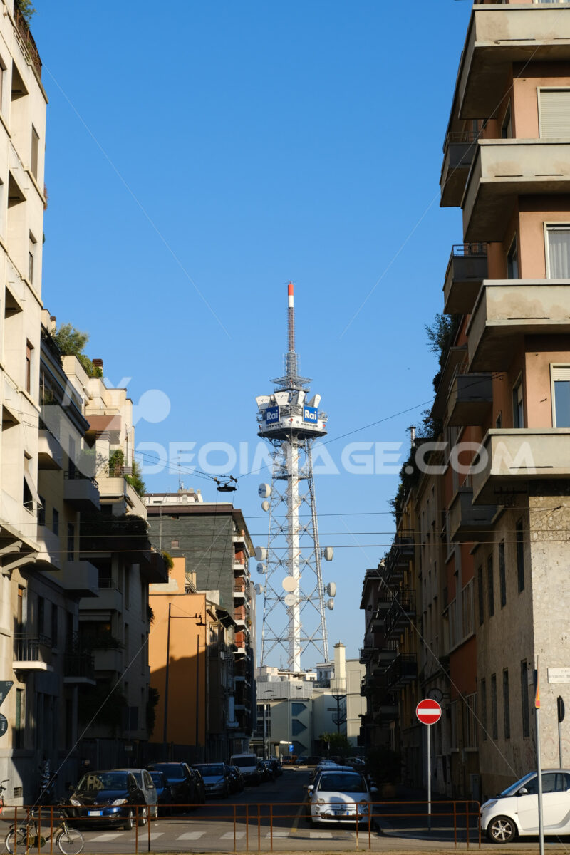 Tower with antennas and TV radio repeaters of the RAI of Milan. Laterally buildings with residential houses. - MyVideoimage.com