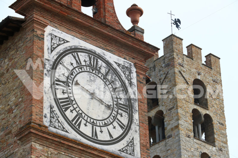 Towers with bell tower and large clock at the church of Impruneta, near Florence. Bell towers in terracotta and stone bricks. - MyVideoimage.com