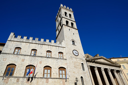 Town hall with flags and clock tower in the square of Assisi. Made with masonry in stone blocks. - MyVideoimage.com