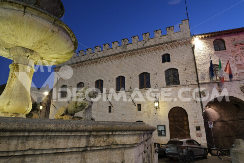 Town square of Assisi with the Palazzo dei Priori and fountain at night. The city of San Francesco with the lights of the night. - MyVideoimage.com