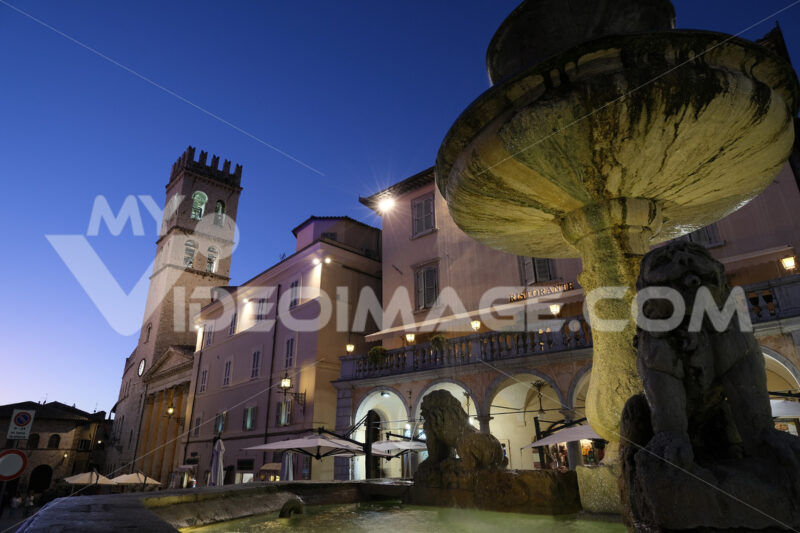 Town square of Assisi with the Torre del Popolo and fountain at night. The city of San Francesco with the lights of the night. - MyVideoimage.com