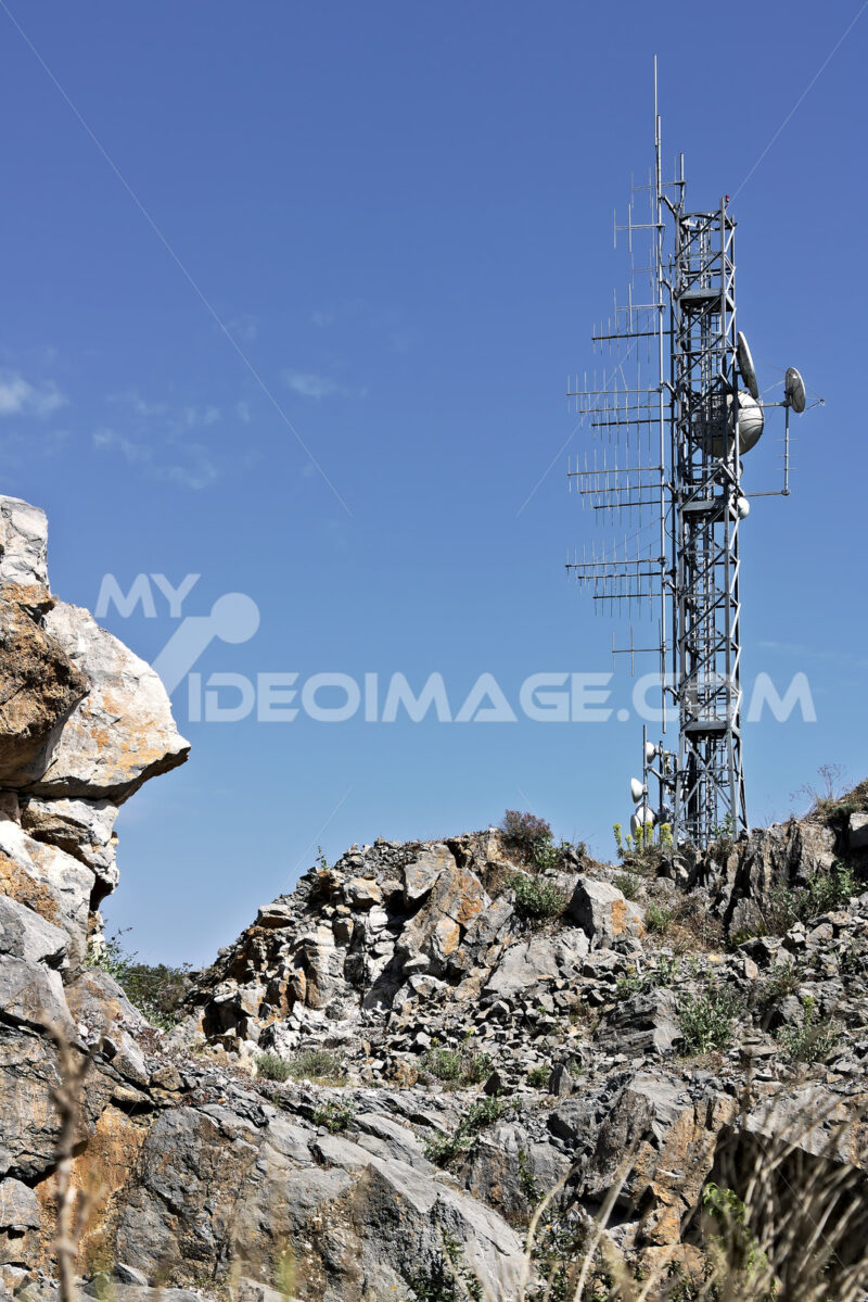 Trellis with numerous transmitting antennas installed on a rocky mountain. - MyVideoimage.com