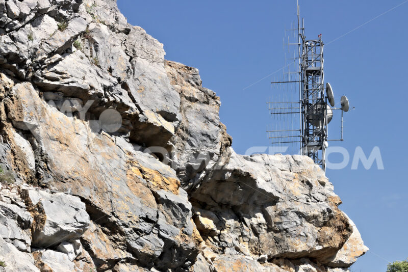 Trellis with numerous transmitting antennas installed on a rocky mountain. - MyVideoimage.com