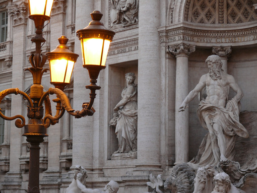 Trevi Fountain at dusk. Travertine marble statues and lit street lamps. - LEphotoart.com