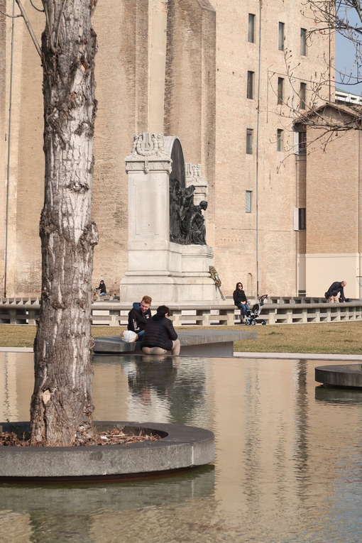 Two people sitting on the edge of a pond. Poplar trees in a tub of water. In the background the Palazzo della Pilotta in Parma. - MyVideoimage.com