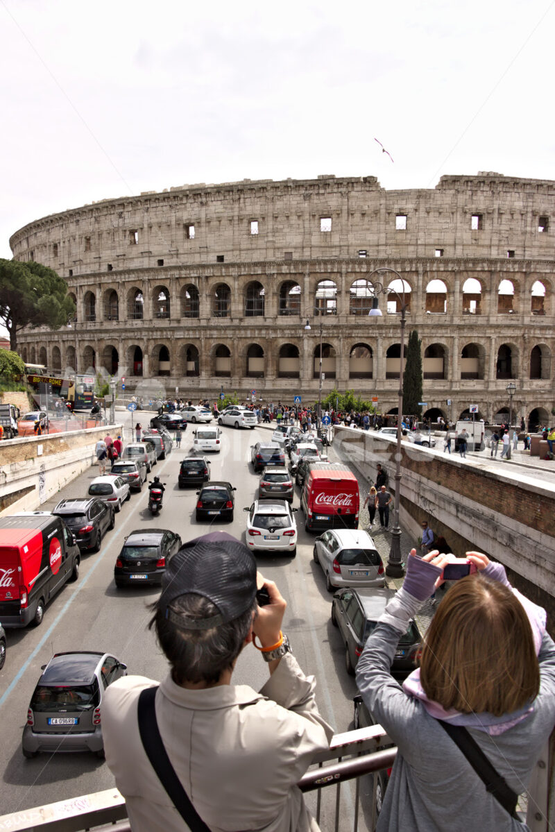 Two tourists photograph the Colosseum. Below you see the road with car traffic and two red vans. - LEphotoart.com