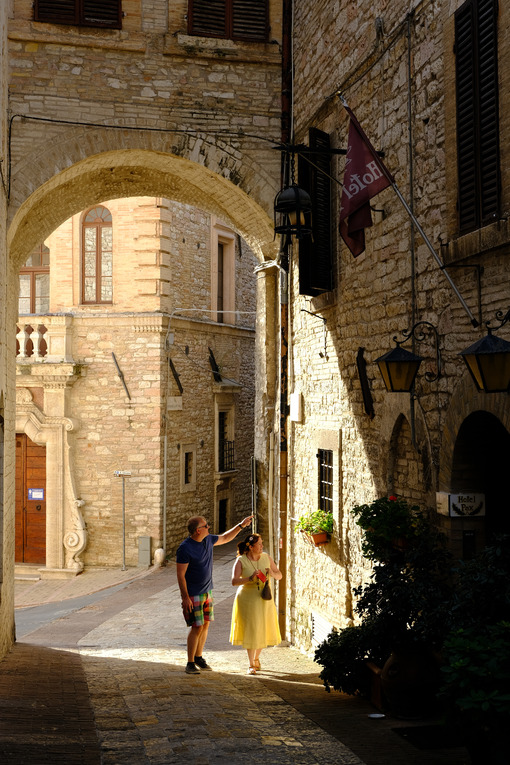 Two tourists walk in an ancient street under an arch in the city of Assisi. The sun illuminates the houses. - MyVideoimage.com