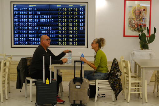 Two travelers sitting at a bar table in Bari airport. On the bottom, the board with the timetable for departing flights. - MyVideoimage.com